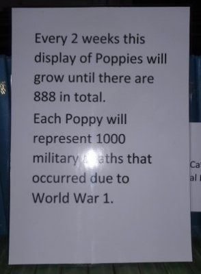 The notice says that the display of poppies is icreased every 2 weeks until there are 888 in total. Each poppy represents 1000 military deaths