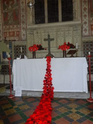 The display of poppies starts from the cross on the altar and spills down onto the church floor increasing in numbers and width as it falls