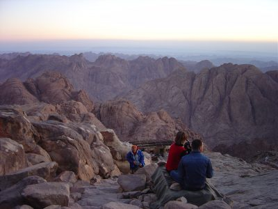 A group of pilgrims stare out over the montains of the Sinai desert