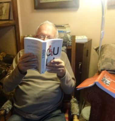 A man in a rocking chair is reading CULL