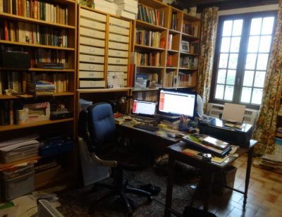 The writer's study lined with bookshelves with a cluttered desk and computer