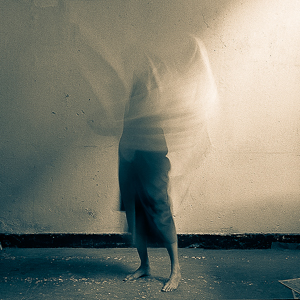 The photo shows the legs and lower body of a young woman who is swirling a white semi-transparent sheet of fabric around the top on her body so that it appears to be disintegrating