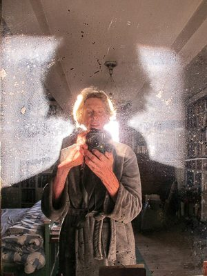 Geraldine is shown taking a photograph of herself in an old glass mirror. The sun is lighting up the back of her head and casting a shadow on the glass