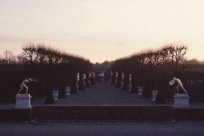The photo shows an avenue lined by pollarded trees and rows of neo-classical statues catching the last rays of the winter sun.