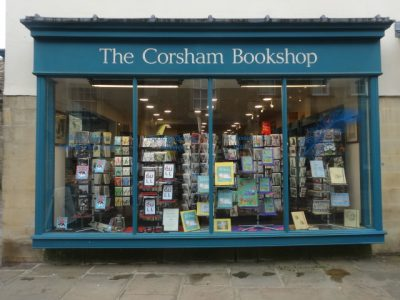 The blue-framed window of Corsham Bookshop with a book display