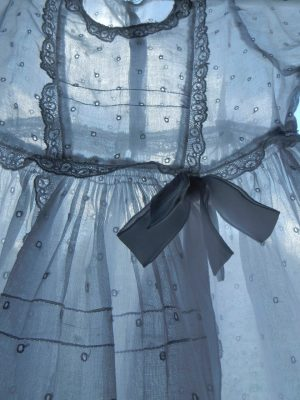 A baby's christening robe is transparent against a lit backgound