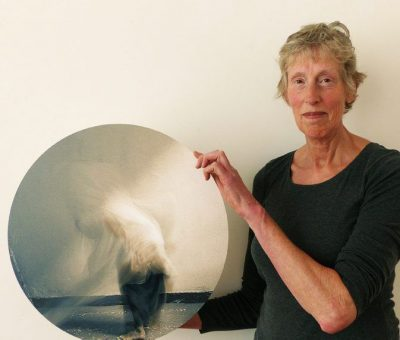 Geraldine is holding a circular photograph in which a moving figure is swirling.
