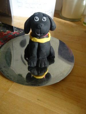 A small black guide dog made of sugar icing