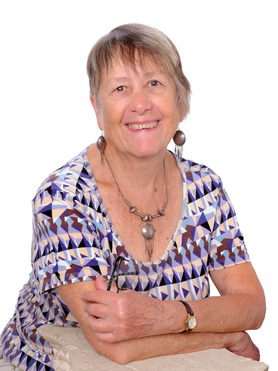 Storyteller Ruth Hartley smiles at the camera. She is wears a pixie haircut and a patterned top with a geometric design in shades of purple and white, with matching silver necklace and earrings.