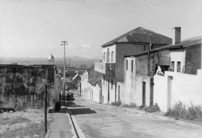 A black and white photo shows a street leading down to the hrbour with slum housing on the right