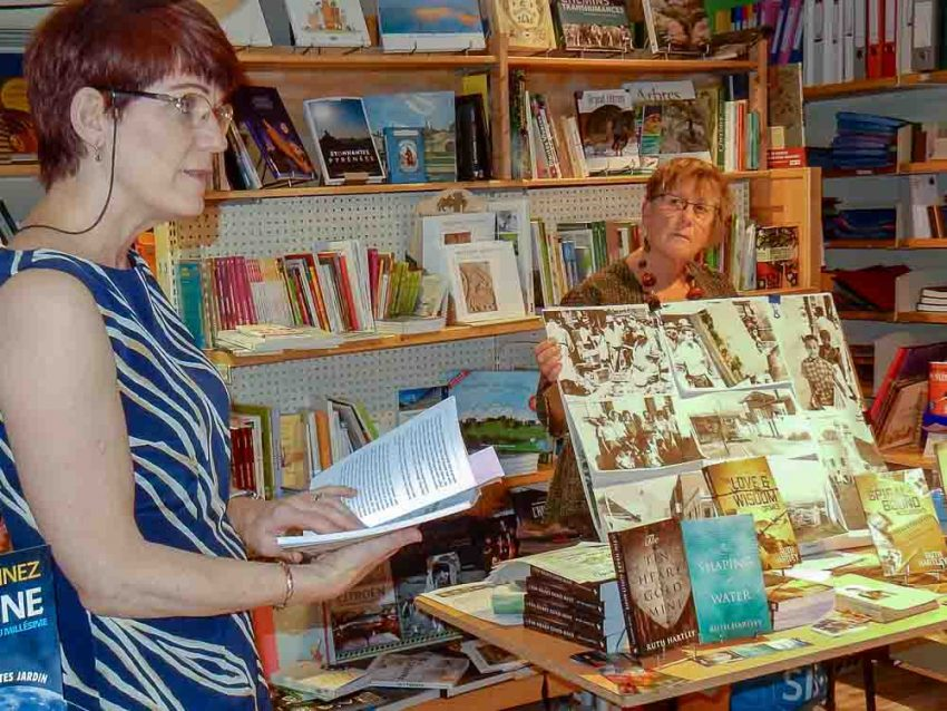 Tia is at the left of the image reading from Ruth's book while Ruth looks on from a table loaded with her books