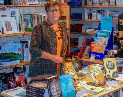 Standing behind a table displaying all her books, Ruth explains the background that substantiates her claim to have taken a lifetime to write the three books launched at La Litote