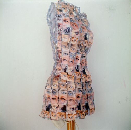 A slim female wire-frame tailors dummy is threaded with photos of the eyes of Princess Diana looking towards press photographers