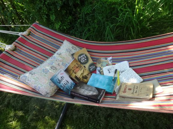 Image shows a striped hammock in which are all 5 of Ruth's published books with pens and notebooks.